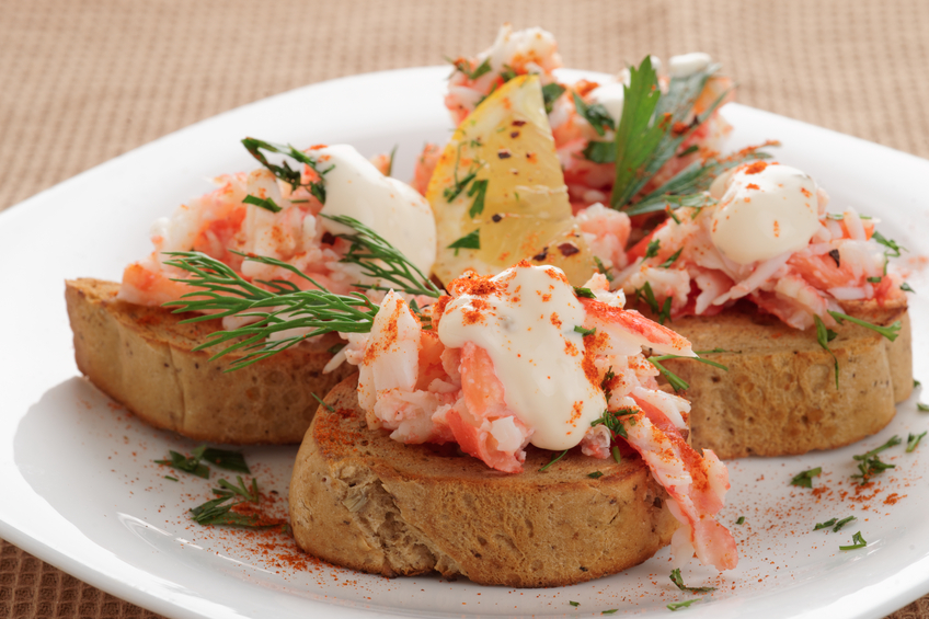 Crab meat with toast in a white plate