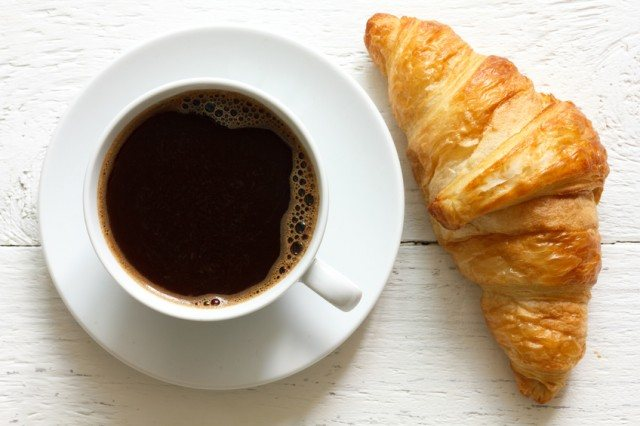 Croissant and coffee on wooden background