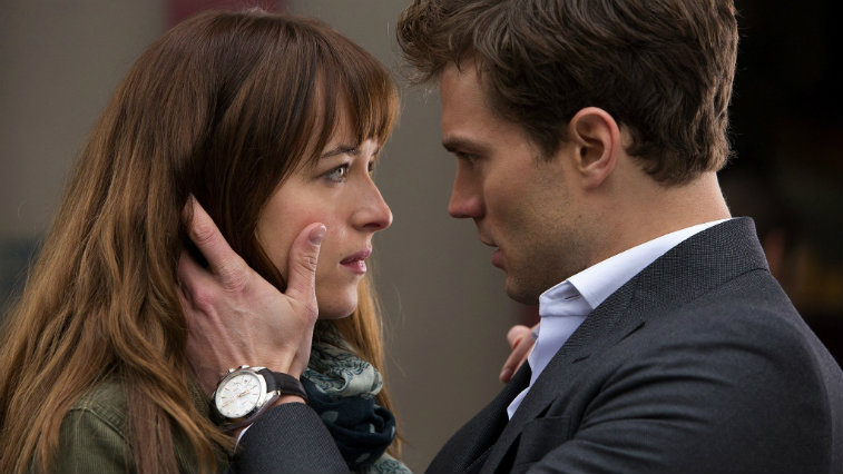 Jame Dornan holding Dakota Johnson's face in his hands, gazing into her eyes intensely