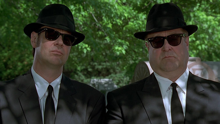 Dan Aykroyd and John Goodman stand next to each other in suits, fedoras and sunglasses