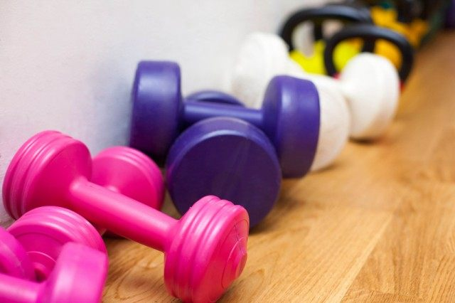 Colorful dumbbells on the gym floor.