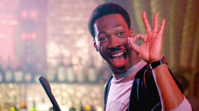 Eddie Murphy smiling in Beverly Hills Cop and giving the a-ok sign