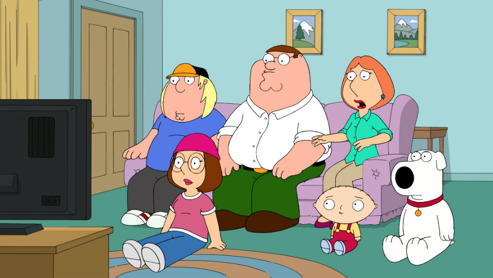 The Griffin family sitting on the couch and the floor watching TV.