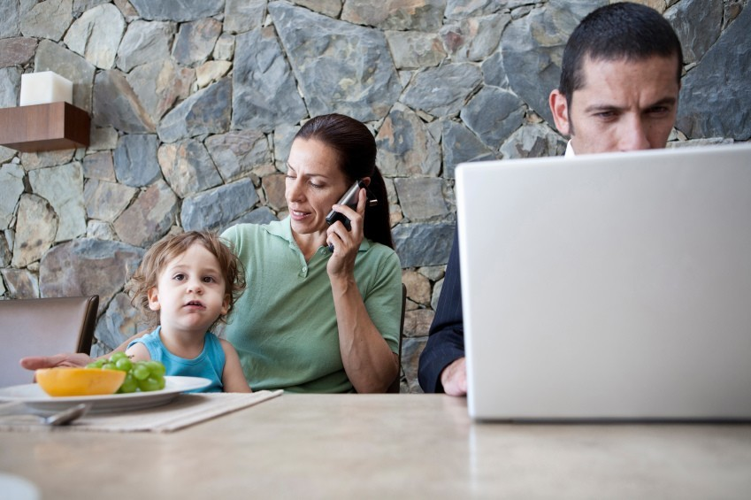 A freelancing mother and father working at the breakfast table with their son
