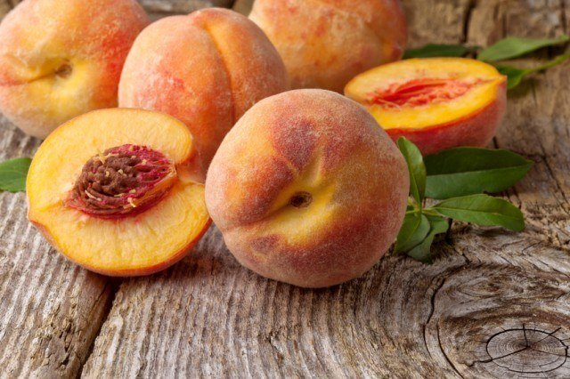 Peaches on wooden background.