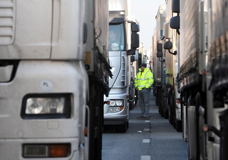 A truck driver waits at a road block, difficult jobs