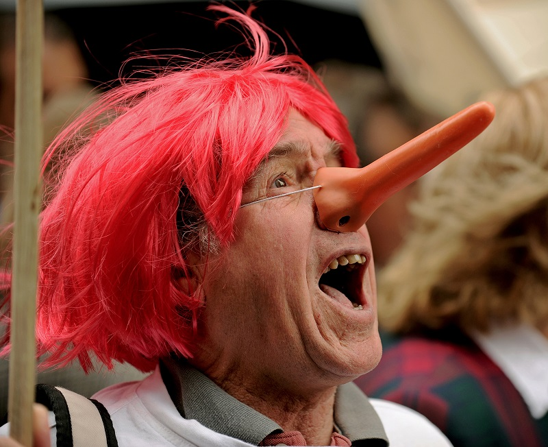A man wears a 'Pinocchio' style nose, emulating the most famous liar of all time