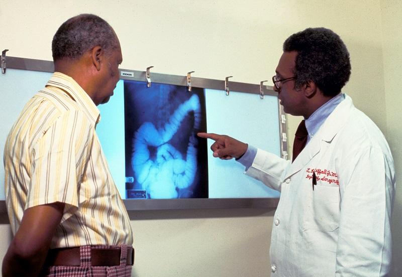 Um médico e um paciente olhando para imagens de câncer
