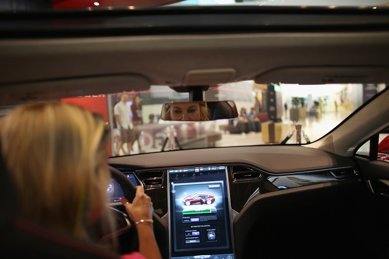 Shoppers check out a new Tesla at a dealership, wishing it was a perk their employers offered