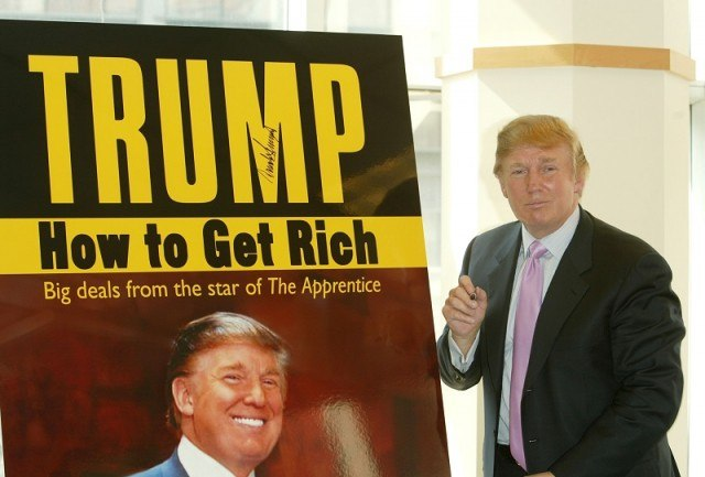 """Donald Trump pauses for a moment after signing a poster depicting the cover of his new book """"How To Get Rich"""""""