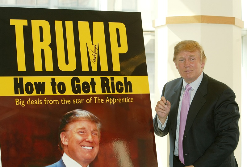 """Donald Trump pauses for a moment after signing a poster depicting the over of his 2004 book """"How To Get Rich"""""""