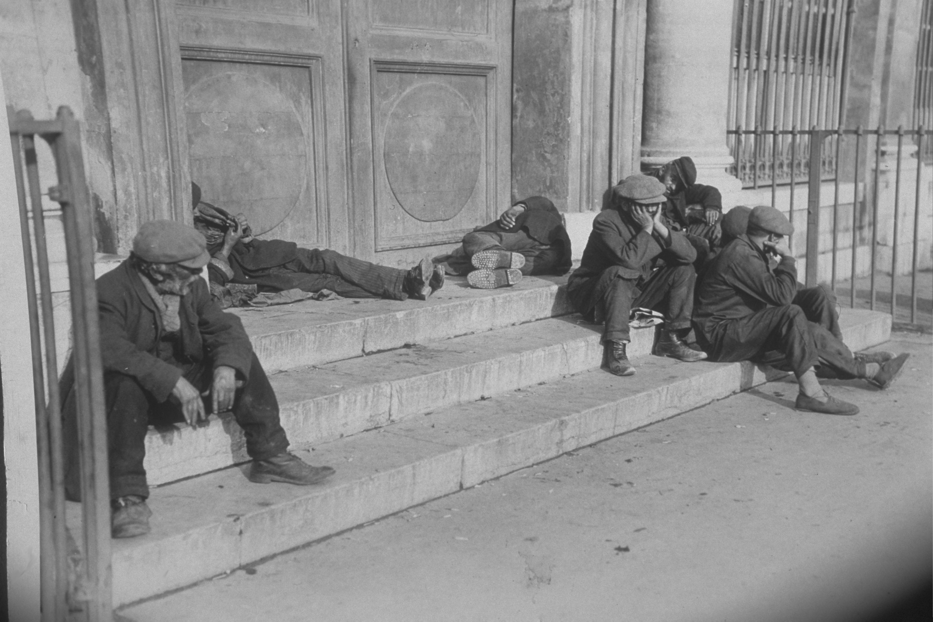 Beggars, suffering from a lack of affordable housing, on the steps of a town hall