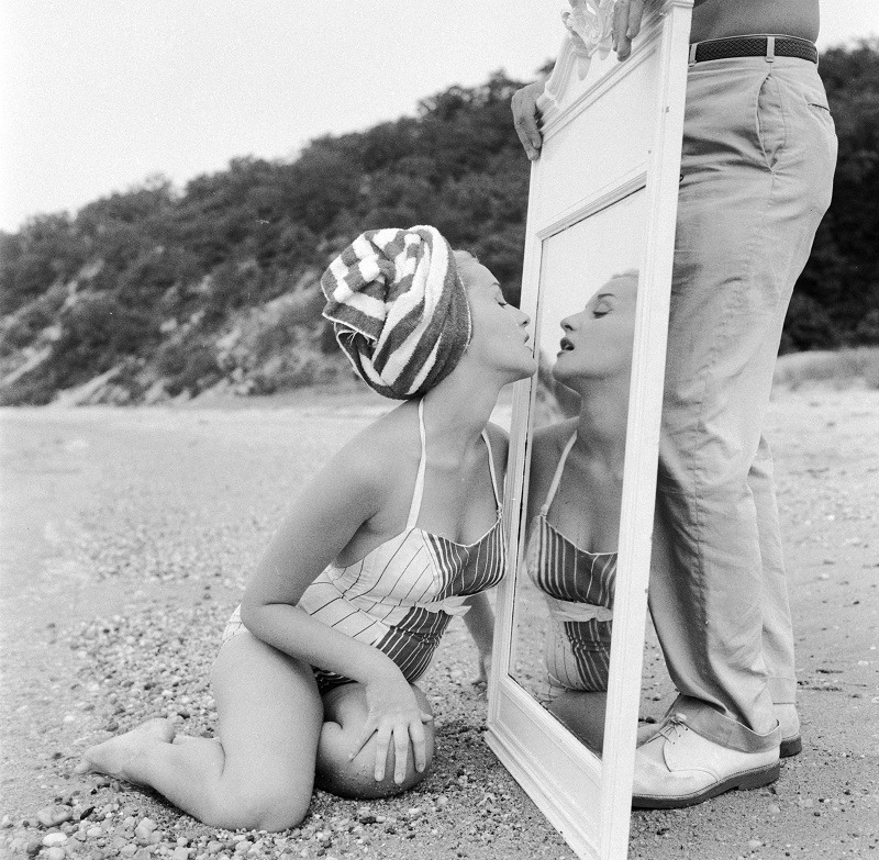 A narcissistic girl on a beach checking her lipstick in a mirror