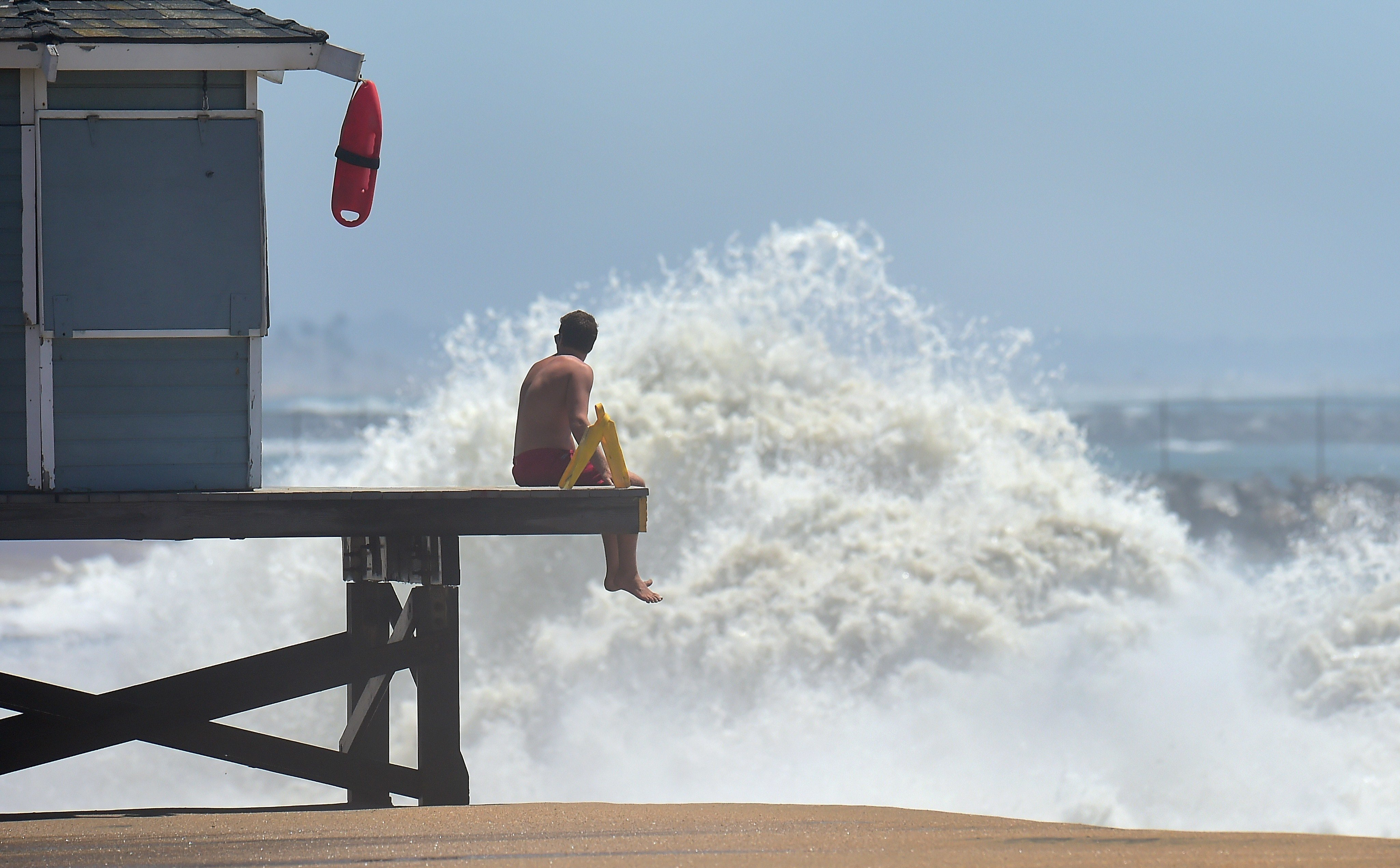 A lifeguard keeps a lookout as big waves crash ashore at Seal Beach, California | Frederic J. Brown/Getty Images
