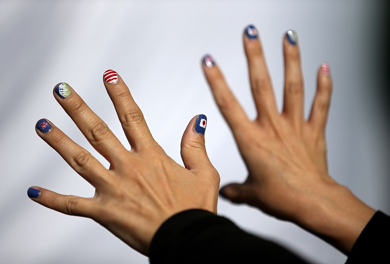 A woman shows her fingernails painted with different flags