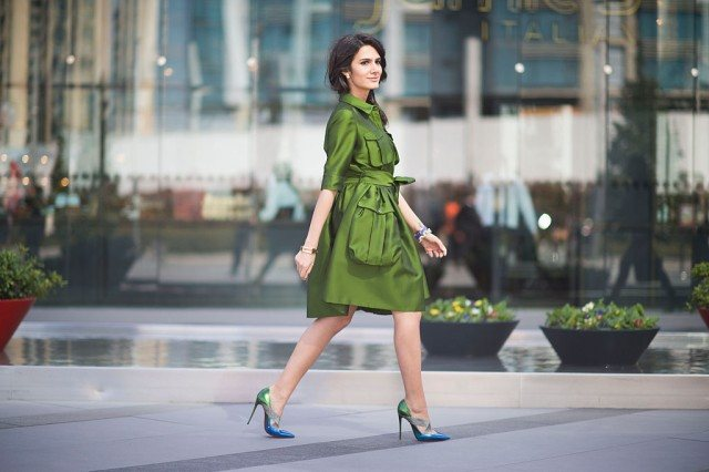Woman wearing a green coat and high-heels