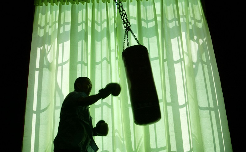 An older man works toward his fitness goals by hitting a punching bag