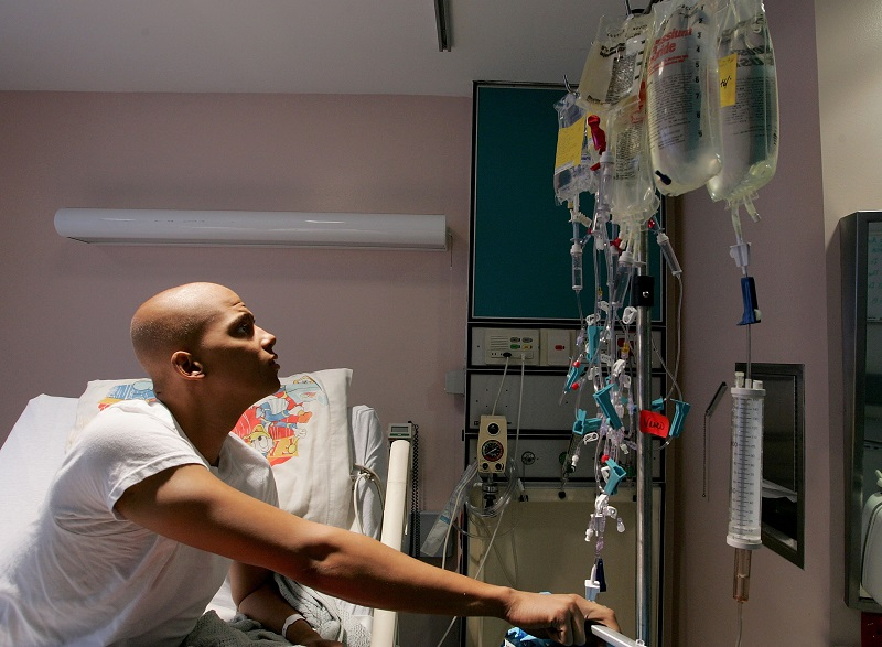 A cancer patient looks at a rack holding bags of chemotherapy while receiving treatment