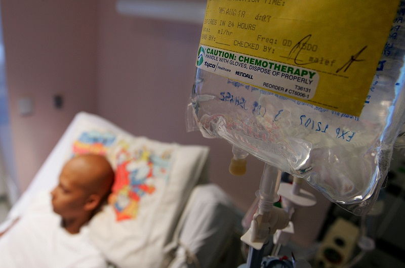 A cancer patient lies in his hospital bed while receiving IV chemotherapy treatment for a rare form of cancer