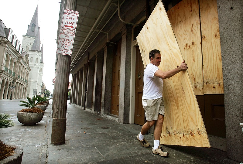 A man boards up a New Orleans store front