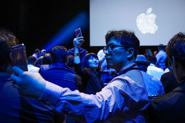 Osen Pilju Kang (C) takes a selfie with the Apple logo, ahead of a Apple's annual Worldwide Developers Conference presentation at the Bill Graham Civic Auditorium in San Francisco, California, on June 13, 2016.