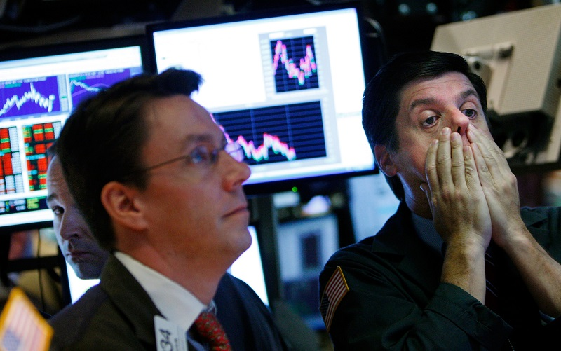 A fearful trader rubs his face while working on the floor of the New York Stock Exchange