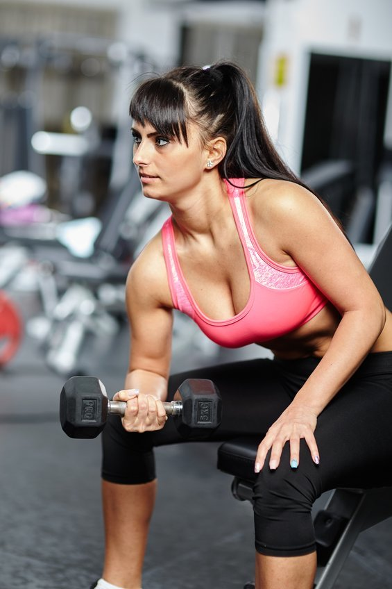 Girl doing biceps in a gym