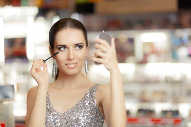 Woman with mascara and make-up looking in a mirror