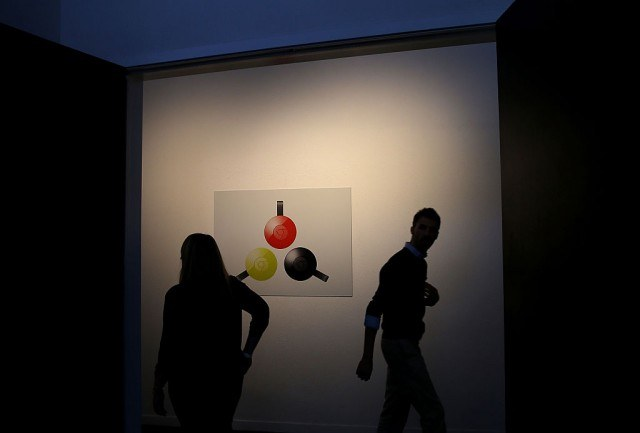 Attendees walk by a poster with an image of the new Google Chromecast during a Google media event on September 29, 2015 in San Francisco, California.