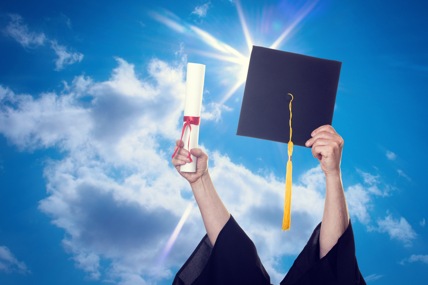 A college grad thrusts his hat to the sky