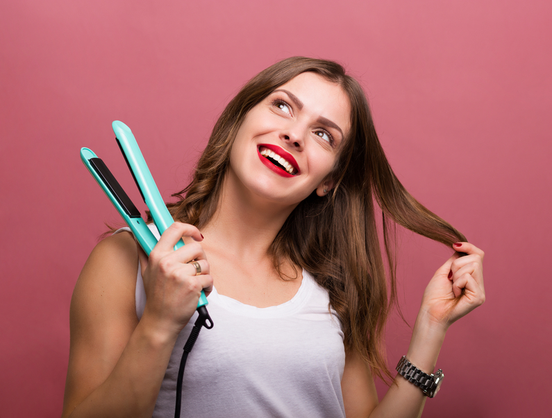 woman styling hair with a heated hair straightener