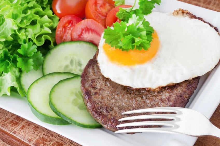 Hamburger with fired egg and salad