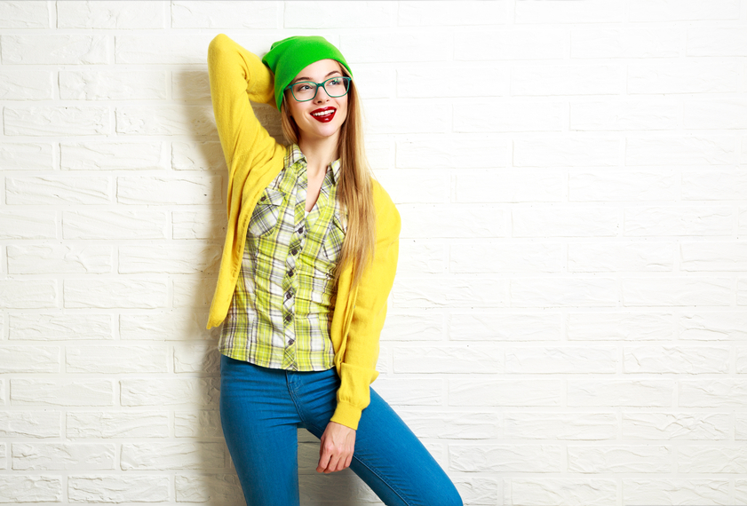 Happy hipster girl standing against the wall