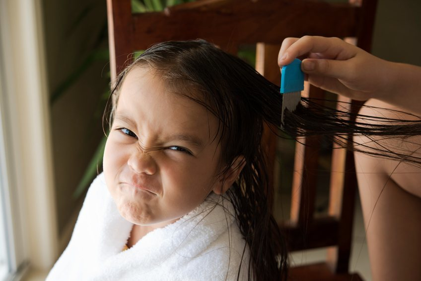 girl getting lice treatment