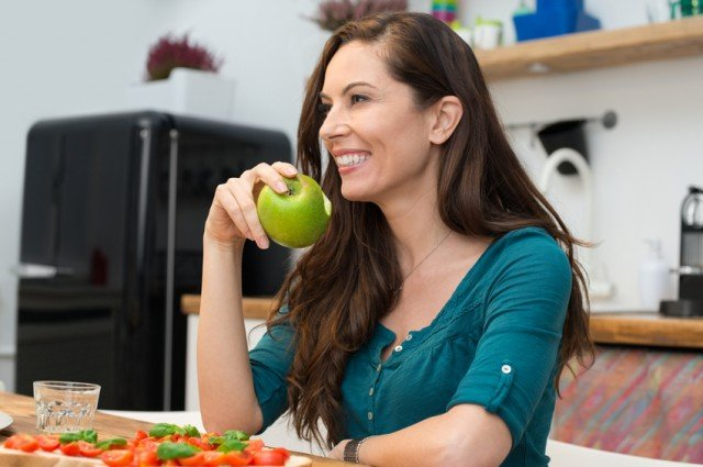 Happy woman eating green apple at a table.