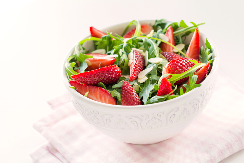 A leafy green salad, with strawberries