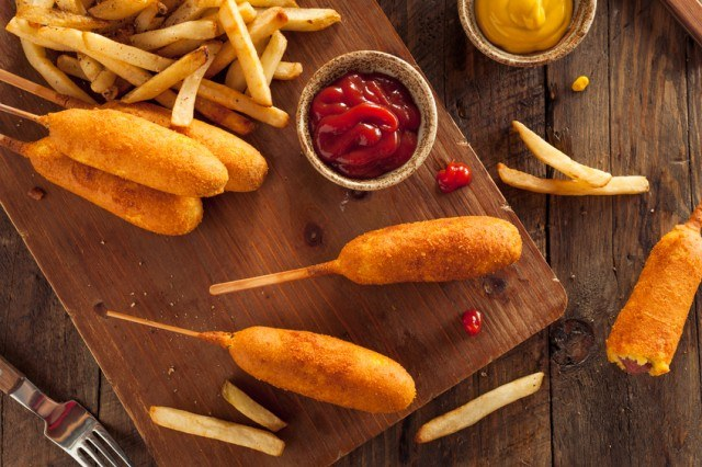 Corn Dogs with fries on wooden board