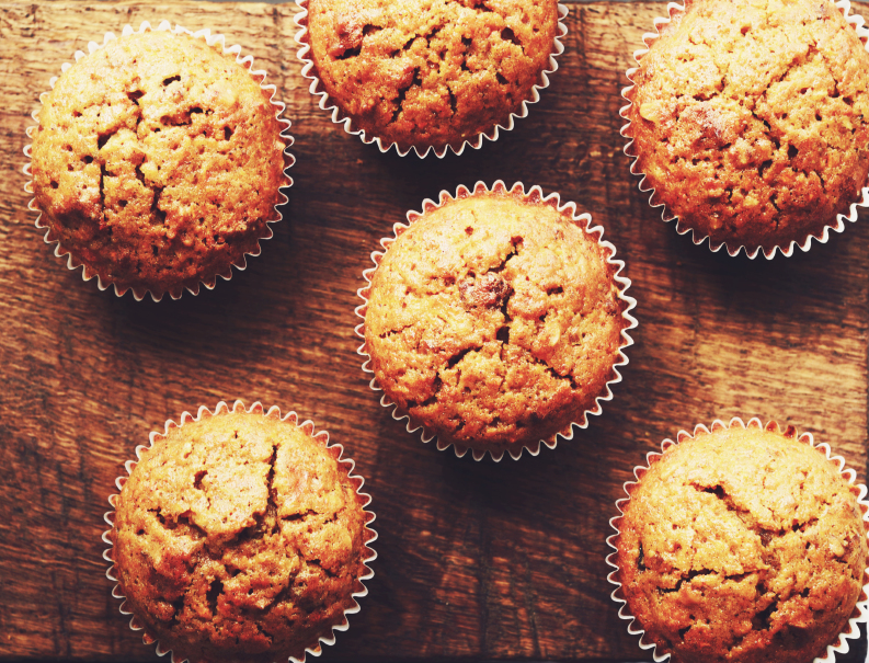 overhead shot of carrot muffins on a wooden counter