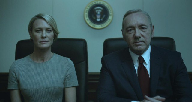 Francis and Claire sit next to each other behind a desk staring straight ahead.