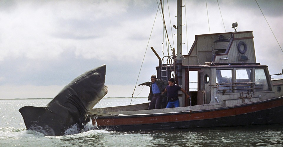 Two men are shocked as a shark is trying to get them on their boat.