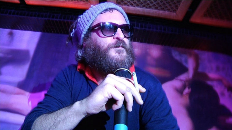 Joaquin Phoenix wearing sunglasses and a knit hat holding a microphone