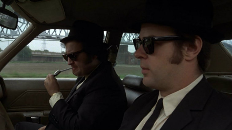 John Belushi and Dan Aykroyd sit in the front seats of a car in suits and sunglasses in The Blues Brothers
