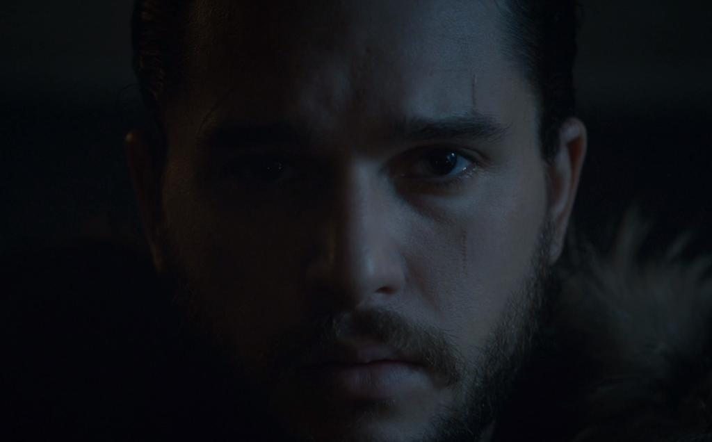 A close up on Jon Snow, with half his face shrouded in shadows