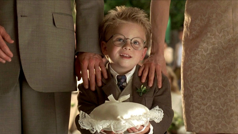 Young Jonathan Lipnicki holds a ring bearer pillow while standing between two adults in Jerry Maguire