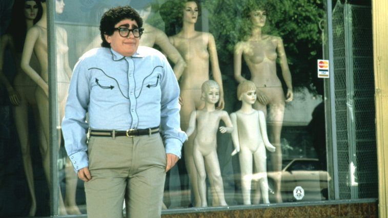 Julia Sweeney stands in front of a storefront window while wearing glasses and shrugging her shoulders in It's Pat