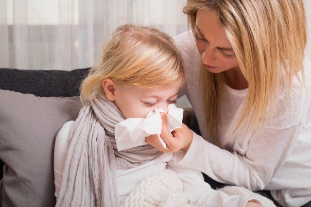 mother helping child in blowing her nose
