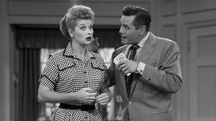 Desi Arnaz holds up a microphone to Lucille Ball in a scene from I Love Lucy