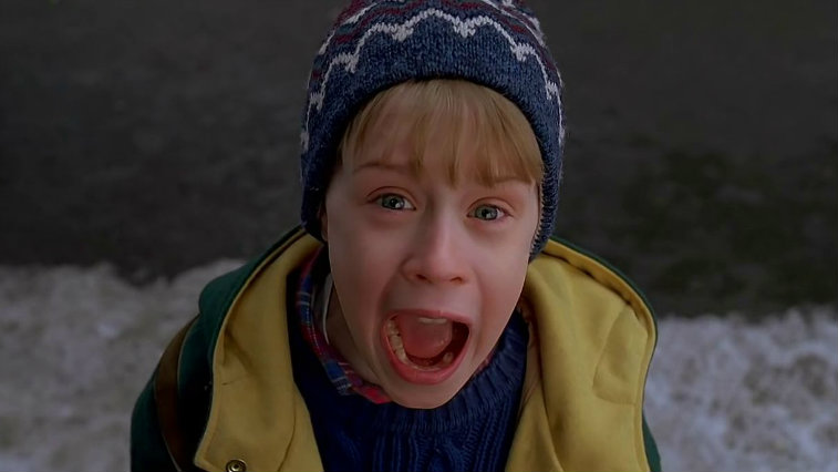 Young Macaulay Culkin screams while wearing a hat and a coat in Home Alone 2