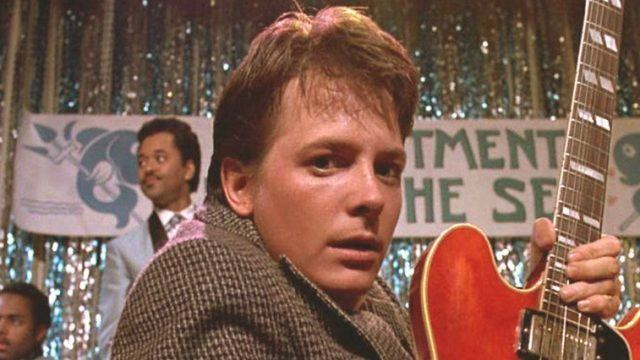 Michael J Fox playing on a guitar on stage in 'Back to the Future'.