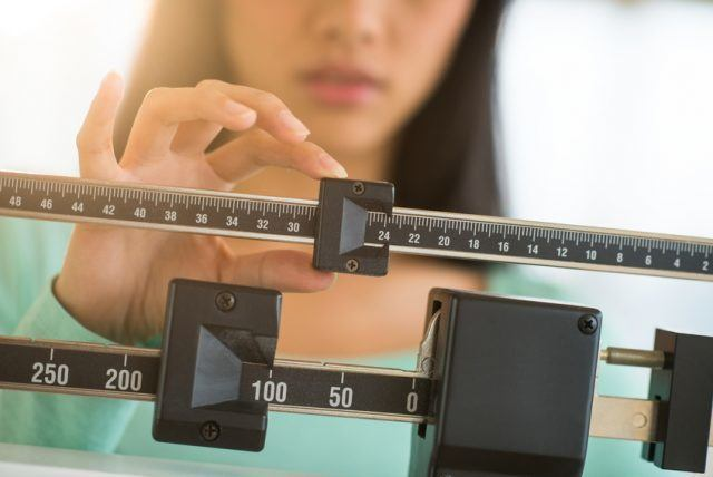 Woman Adjusting Weight Scale